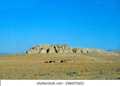 Jordan, arid landscape and poorly looking huts with flock of goat and shepherd