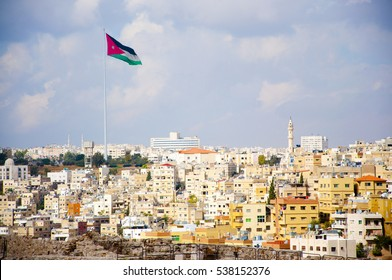 Jordan flag in Amman with houses