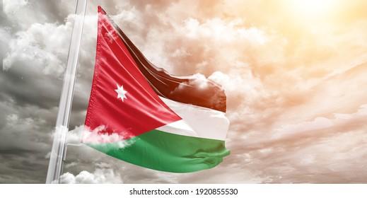 Jordan national flag cloth fabric waving on beautiful grey sky.