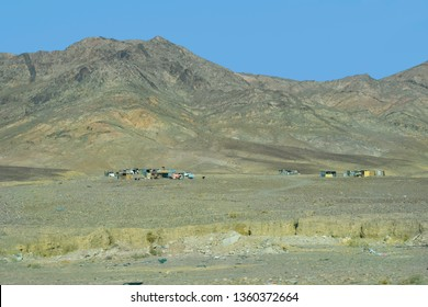 Jordan, poorly looking Bedouin camp and goats in arid landscape