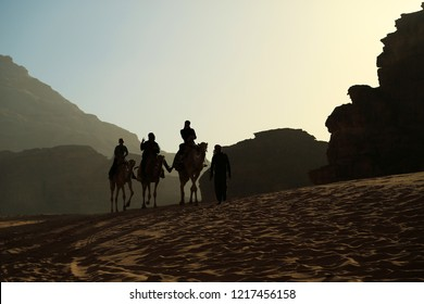 JORDAN, WADI RUM DESSERT, DECEMBER 5, 2016: JPeople rides on camels in Wadi Rum desert, also known as Valley of the Moon, is largest wadi in Jordan. Wadi is a term traditionally referring to a valley