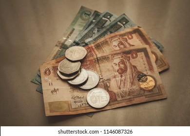 Jordanian dinars and piastres lay on gray paper background, close-up vintage stylized photo with tonal filter effect