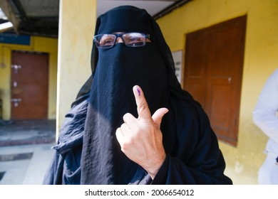 Jorhat,Assam,India-27 March 2021: A Muslim Woman wearing burka shows  her  finger marked with indelible ink after casting her  vote in  Jorhat.
