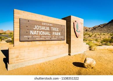 Joshua Tree National Park Entrance, Twentynine Palms, California, USA - May 14, 2018: Entering Joshua Tree NP sign and NPS service logo on wooden arrowhead, brick wall and desert landscape background
