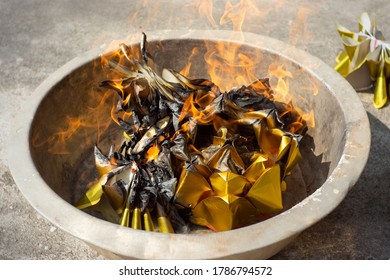 The joss paper is folded in half, or folded into a shape of a gold are burning in metal bucket  - belief in China that if you burn paper money and make offerings at the graves of your ancestors,