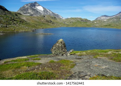 Jotunheimen National Park. Mountain lake surrounded by peaks and a large stone on the shore. Sunny summer day