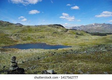 Jotunheimen National Park. Mountain rocky valley with a lake surrounded by peaks and Cairn on the shore. Sunny summer day