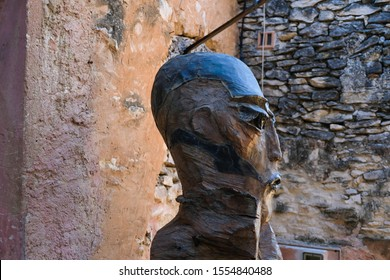 Joucas. Luberon. Provence. France. October 05. 2019. Head of a gigantic man sculpture made of wood and metal on a wall background. Man's look. France tourism.