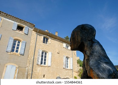 Joucas. Luberon. Provence. France. October 05. 2019. The gigantic man sculpture looks in the direction of the window of the house opposite. In the open window toy bears.