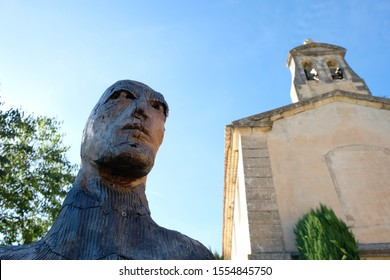 Joucas. Luberon. Provence. France. October 05. 2019. Fragment of a sculpture of a giant man made of wood and metal near an ancient church. Man's look. France tourism.