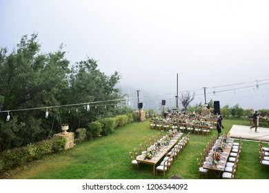 Jounieh / Lebanon - 8/8/2018 - Arabian Celebration Preparation in the top of mountain in Lebanon - tablets and chairs and light on the grass and Mountain clouds in background