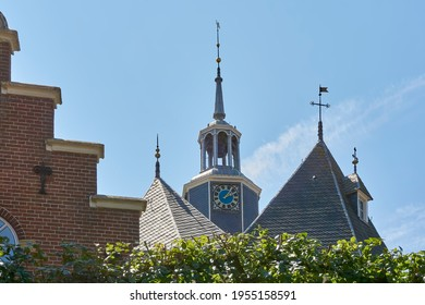 Joure, The Netherlands - July 15 2018: View on the Jouster Toren or Jouster Toer in Joure against a blue sky. In the front a house with a stepped gable.