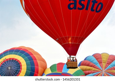 JOURE, THE NETHERLANDS - JULY 19, 2019:  Large red hot air balloon with basket and people rising above multi coloured balloons during the 34th Friese Ballonfeesten festival in Joure The Netherlands.