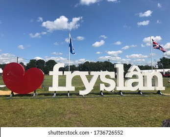 Joure, Netherlands, June 25, 2019: large white letters of logo of province of Friesland against background of green field and blue sky. Next to it is big red plastic heart. Near two flags on flagpoles