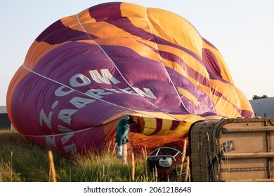 Joure, The Netherlands on July 19, 2021: Adult man filling a hot air in balloon. Ballooning is a growing business in the Netherlands.