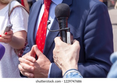 Journalist holding microphone making media interview with business person