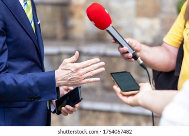 Journalist holding microphone making media interview with politician or business person
