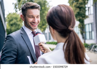 journalist holding microphone and talking with businessman in formal wear