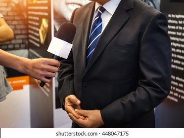 Journalist With Microphone Interviewing Businessman, politician