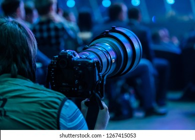 Journalist photographer with a telephoto lens at work, back view