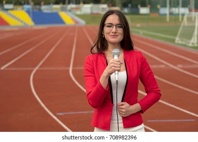 The journalist is reporting from the stadium for television
