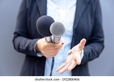 Journalist or TV reporter holding microphone and making media interview. Broadcast journalism concept.