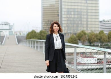 journalist, woman in business clothes go to work. Smiling middle-aged American lady wearing black jacket skirt and white blouse talking with friend on mobile. Concept of innovative technologie