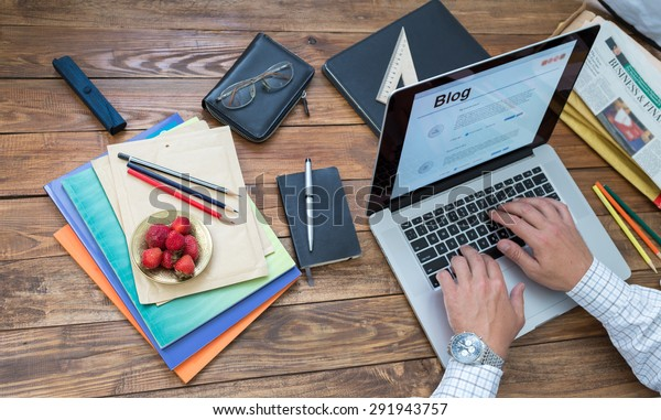 Journalist working on his new article. Overhead view of man typing on keyboard laptop located vintage natural wooden desk with many items in creative messy disorder