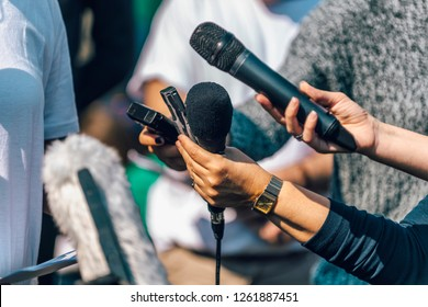 Journalists holding microphone and dictaphone, interviewing female speaker.