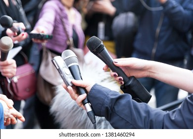 Journalists holding microphones at press conference