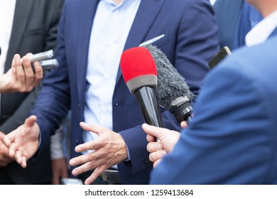 Journalists making media interview with businessperson or politician at news conference