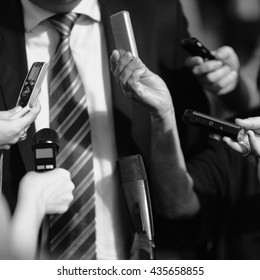 Journalists surrounding politician, asking questions. Retro style black and white processing