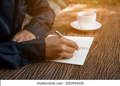 journalists are writing down important events or headlines on a diary.Business working concept. Blogger writing new article in coffee shop