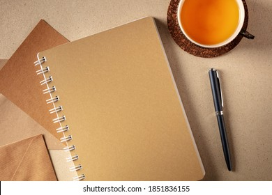 Journalling concept. Brown paper journal, top shot on a desk with a cup of tea and a pen, the concept of free writing