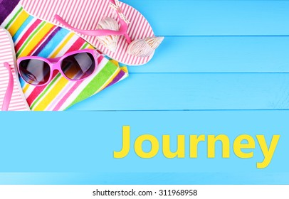 Journey concept. Beach accessories on blue wooden background