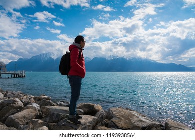 A journey man standing on a rock and look at mountains and lake, lake Geneva, Vevey, Switzerland in Freedom and Adventure concept