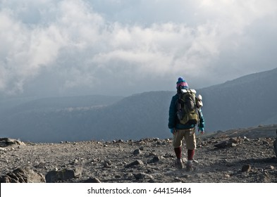 journey over the mountains, the image of a old man tracking along rocky path at high altitude in Japan.
