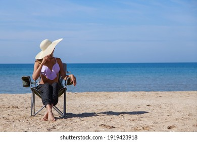 journey to the sea. girl in a bathing suit and hat sunbathing on the beach. tourist sitting on the sand. leisure wear. copy space