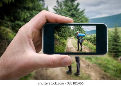 journey through the mountains, photo tourist, tourist photographing people on the smartphone, phone in hand