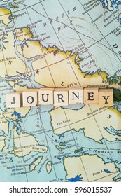 Journey word made from wooden letter blocks on a vintage map. Travel, holiday concept