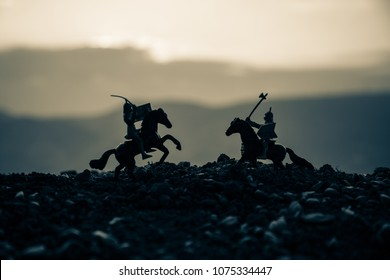 Joust between two knights on horseback. Sunset on background.