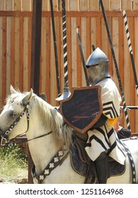 Jousting knight riding a white horse holding a lance