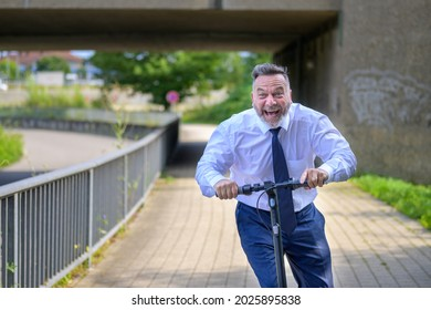 Jovial businessman yelling in pure enjoyment as he speeds along on an electric scooter approaching the camera along a walkway beside a highway