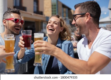 jovial friends toasting with their drinks glasses