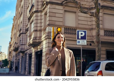 A jovial lady crossing the street carefully with a smile and holding onto her bag