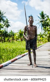 JOW VILLAGE IN JUNGLE, ASMAT DISTRICT, NEW GUINEA, INDONESIA - JUNE 4: Portrait of Headhunter of a Papuan Asmat tribe with spear. June 4, 2016, Asmat area, Irian Jaya province, Indonesia