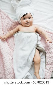 It's a joy to be clean. Happy beautiful dark hair baby smiling and laying down in towels after a bath.