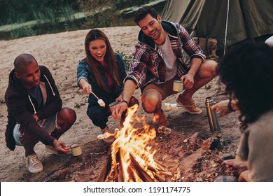 Joy of camping. Group of young people in casual wear roasting marshmallows over a campfire while resting near the lake