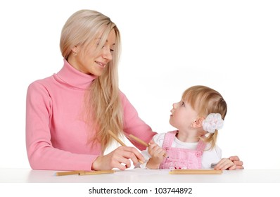 A joy Caucasian mother with her daughter paint crayons on a white background