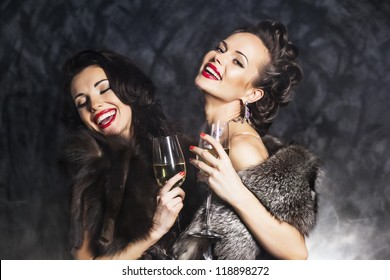 Joy. Elation. Couple of Rich Women Laughing with Crystal of Champagne. Luxury